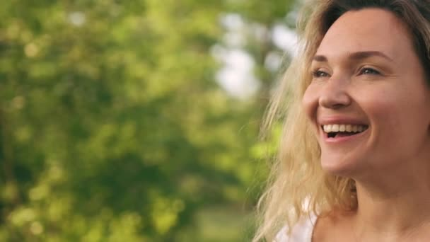Mosolyogva egy boldog felnőtt nő arcára, aki félrenéz a természetben. Vidám felnőtt lány a parkban. Szabadtéri portré egy szőke nőről, hosszú göndör hajjal a parkban. Lassú mozgás..