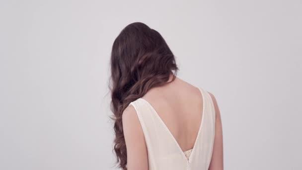 Mädchen dreht sich um und blickt in die Kamera. schöne Frau mit langen braunen Haaren. attraktives Mode-Model mit fliegendem lockigem Haar. schöne brünette Frau schüttelt die Haare. Zeitlupe. 4k Filmmaterial.