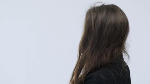Die junge Frau dreht sich um und blickt in die Kamera. Porträt eines schönen ruhigen Mädchens mit langen braunen Haaren, das im Studio posiert. 4k Filmmaterial einer schönen brünetten Frau in einem schwarzen Anzug. Zeitlupe.