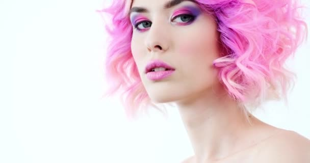 Closeup portrait of a fashion model with bright purple hair.  Stylish woman with fashion hairstyle. Beauty face with a pink makeup. Fashionable girl.  Attractive model turns to the camera. Slow motion