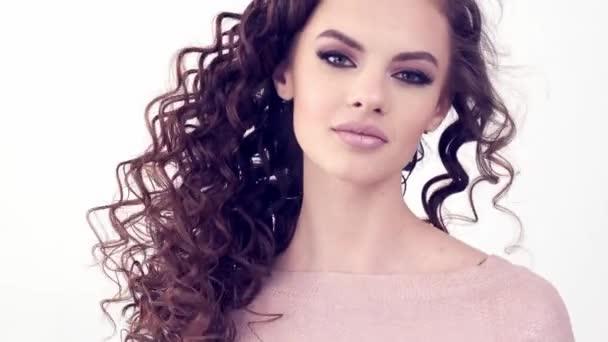 Gyönyörű nő hosszú göndör hajjal. Szépség arc. Divatmodell. Divatsmink. Vonzó lány füstös szemfestékkel. Közelkép egy lányról. Lassan mozgó 4k felvétel. Szexi barna hölgy.