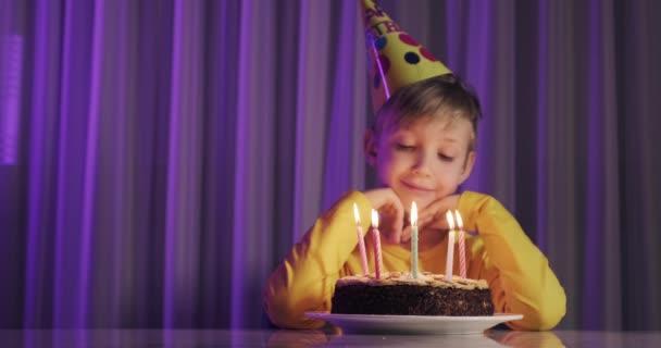Boldog gyermek néz egy tortát gyertyákkal. A gyerek ránéz a tortára, és szülinapi kívánságot tesz. A fiú ünnepli a születésnapját. Boldogság fogalma