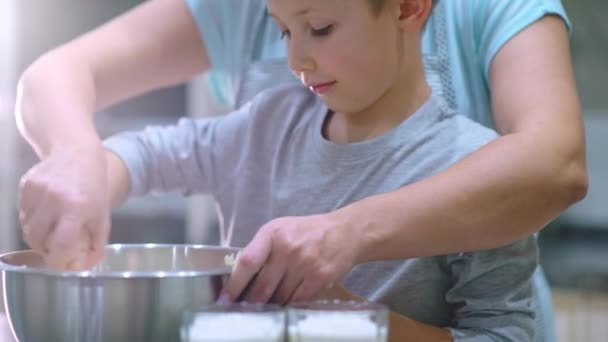Slow motion 4k footage - Mother and child stirring dough in steel bowl. Boy with mom cooking on the kitchen. Family cooking food at home. Mama with a son mixing ingredients for baking cookies