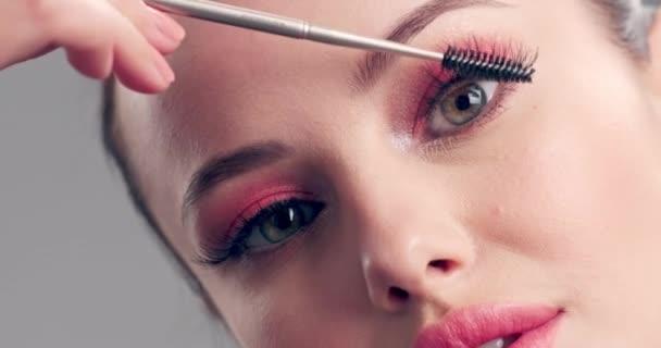 Frau macht Make-up. Die junge Frau bemalt ihre Wimpern mit einem Wimpernpinsel. Kosmetisches Konzept. Schöne brünette Modell beim Make-up. 4k Zeitlupenaufnahmen. Nahaufnahme.