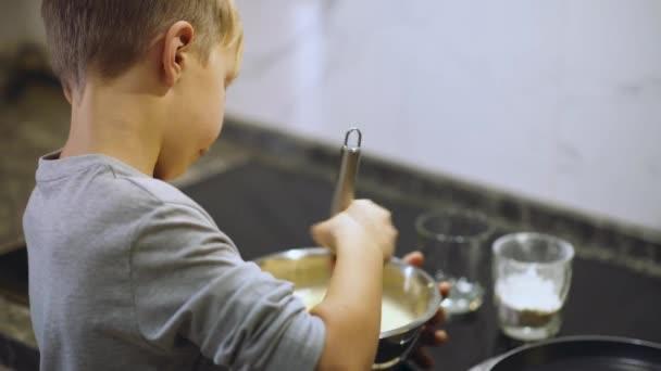 8 éves fiú főz a konyhában. A gyerek habverővel korbácsolja a palacsintakeveréket egy vastálba. A fiú összekeveri a lisztkeveréket a sütikhez. Ebédidő. A gyermekkor fogalma.