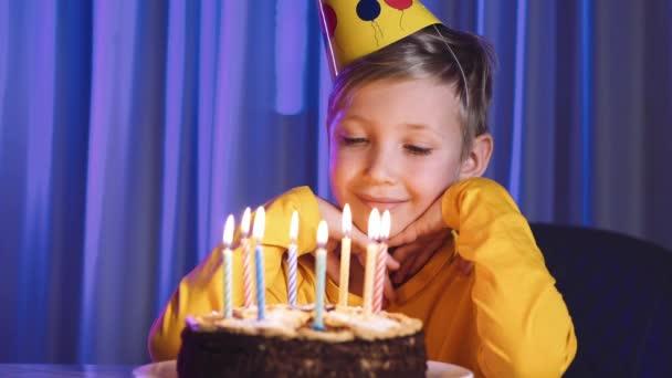 Roztomilý chlapec sfoukne svíčky na dortu na své narozeniny. Šťastné dítě se dívá na dort se svíčkami. Dítě se podívá na dort a přeje si narozeninové přání. Ten kluk slaví narozeniny. Koncept štěstí