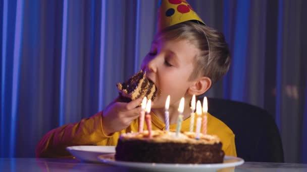 Roztomilý chlapec jí dort na své narozeniny. Šťastné dítě si vezme kousek slavnostního dortu, pak ho kousne a spolkne. Šťastný bílý chlapec slaví narozeniny. Bělošské veselé dítě a narozeninový dort