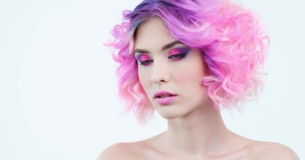 Stylish woman with fashion hairstyle. Closeup portrait of a fashion model with bright purple hair. Beauty face with a pink makeup. Fashionable girl.  Woman turns her head  and looks to the camera.