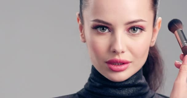 Woman makes makeup. Young woman makes  blush on the face  using makeup brush. Cosmetic concept. Beautiful brunette model doing make-up. Girl runs a makeup brush over her face.  4k Slow motion footage