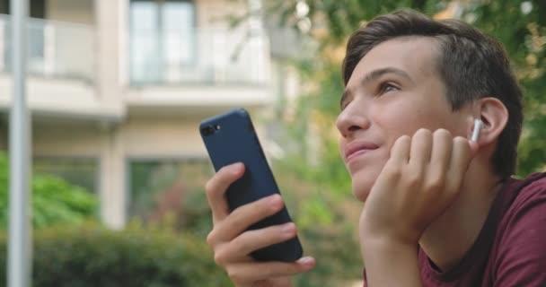 Teen pomocí mobilního telefonu v parku. Usmívající se mladík z mobilu, venku. Šťastný chlapec teenager s mobilním telefonem. Městská scéna. Fešák používá smartphone. 4k. Reálný čas.