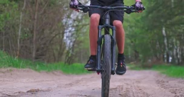 Pohled zepředu na muže v cyklistické helmě, který v létě jezdí na kole MTP. Mladý cyklista jezdí na lesní cestě. Teenager na horském kole projíždí lesem. Záznam v reálném čase
