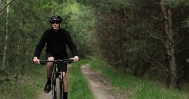 Mladý cyklista jezdí na lesní cestě. Teenager na horském kole projíždí lesem. Muž v cyklistické helmě jezdí na kole MTP.