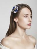 Gyönyörű, vonzó barna modell lány, elszigetelt fehér, kék, sárga és fehér barrette.