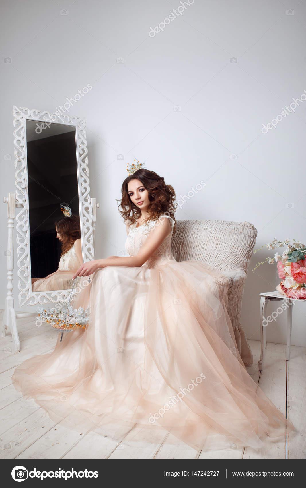 Schöne Braut posiert in Pfirsich Hochzeitskleid auf Sofa in einem ...