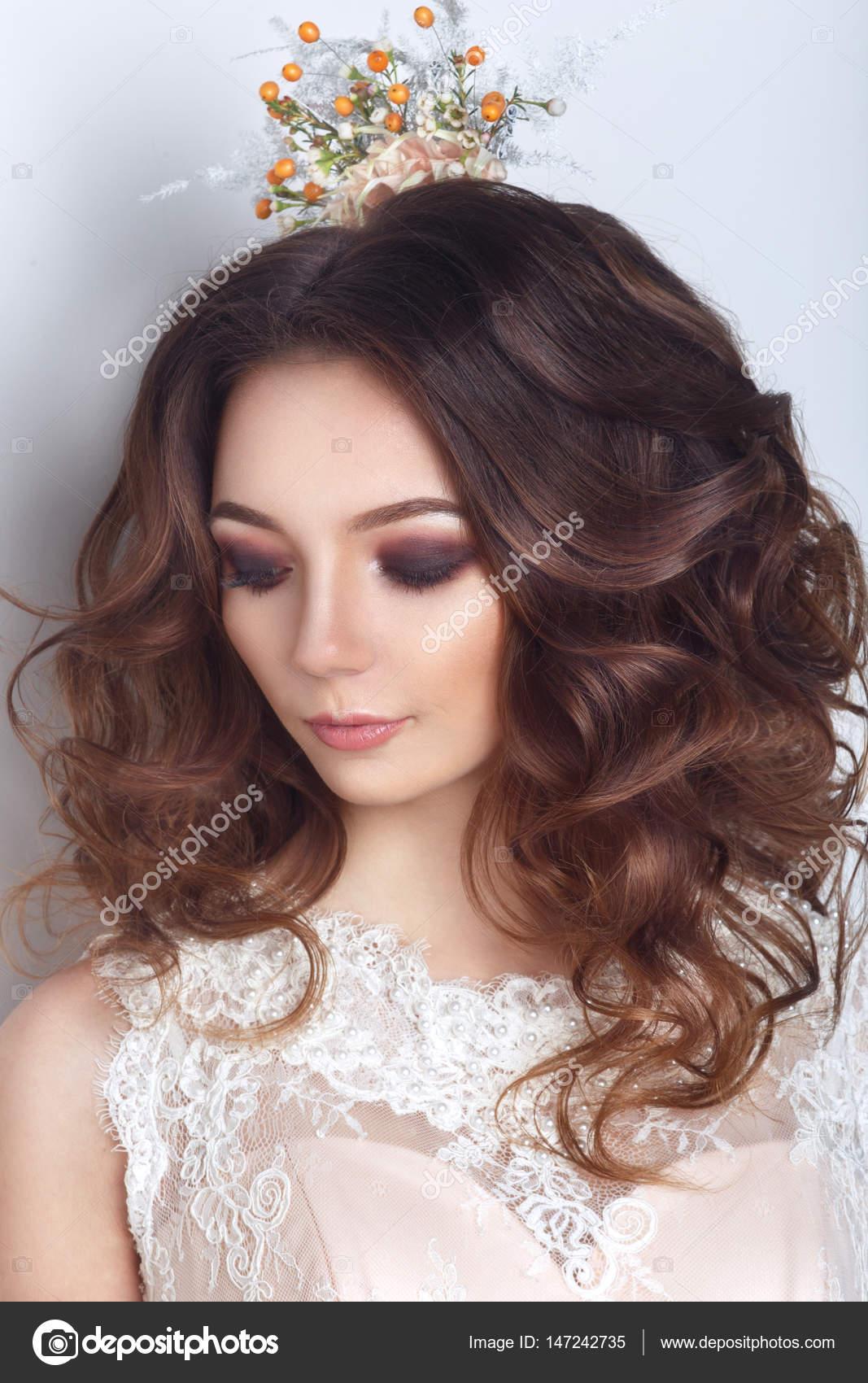 Schöne Braut posiert in Pfirsich Hochzeitskleid und Blume Krone in ...