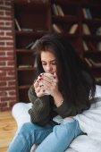 Krásný smutný bruneta žena s šálkem kávy nebo čaje