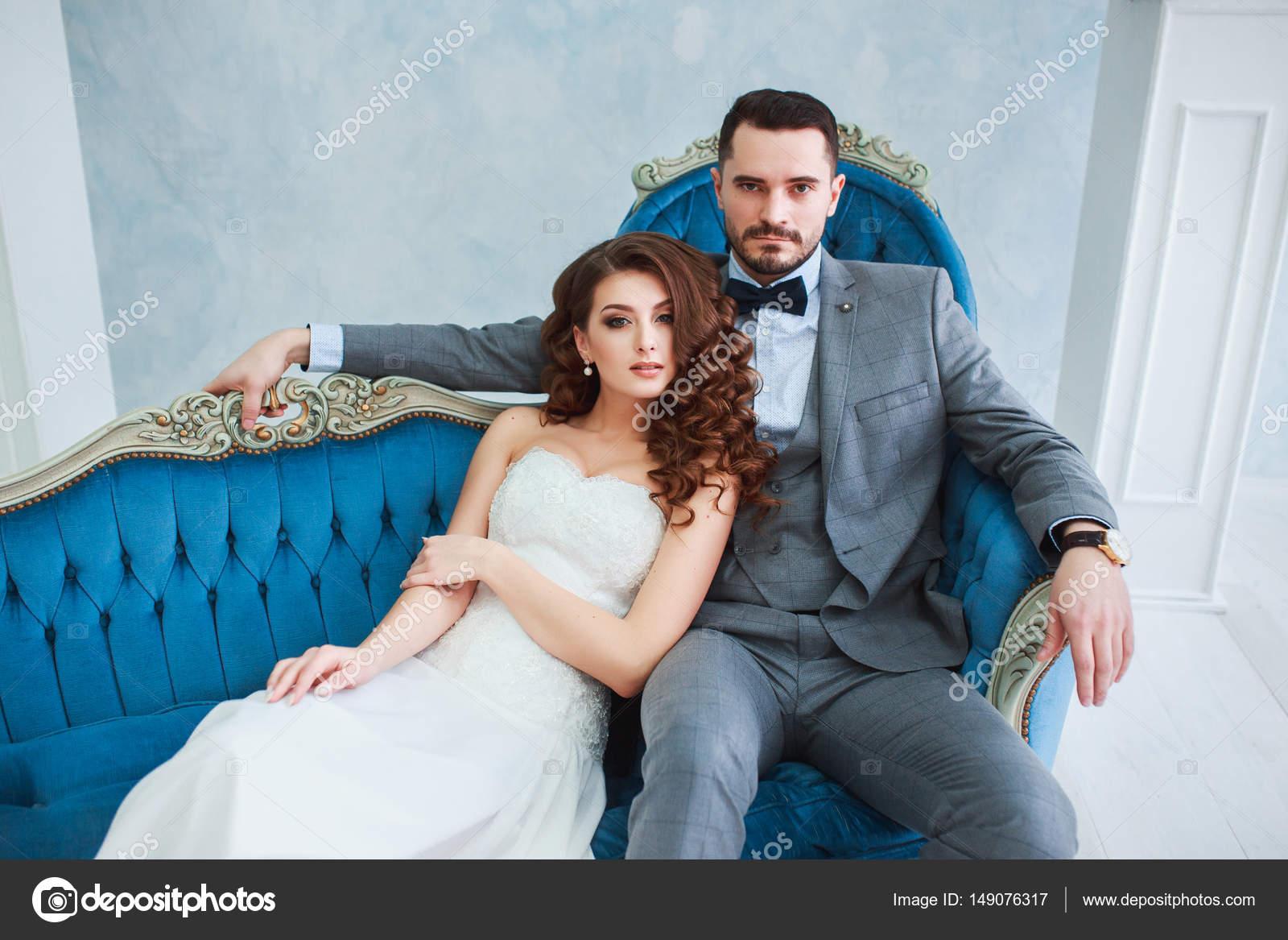 Novia en vestido hermoso y novio en traje gris, sentado en el sofá ...
