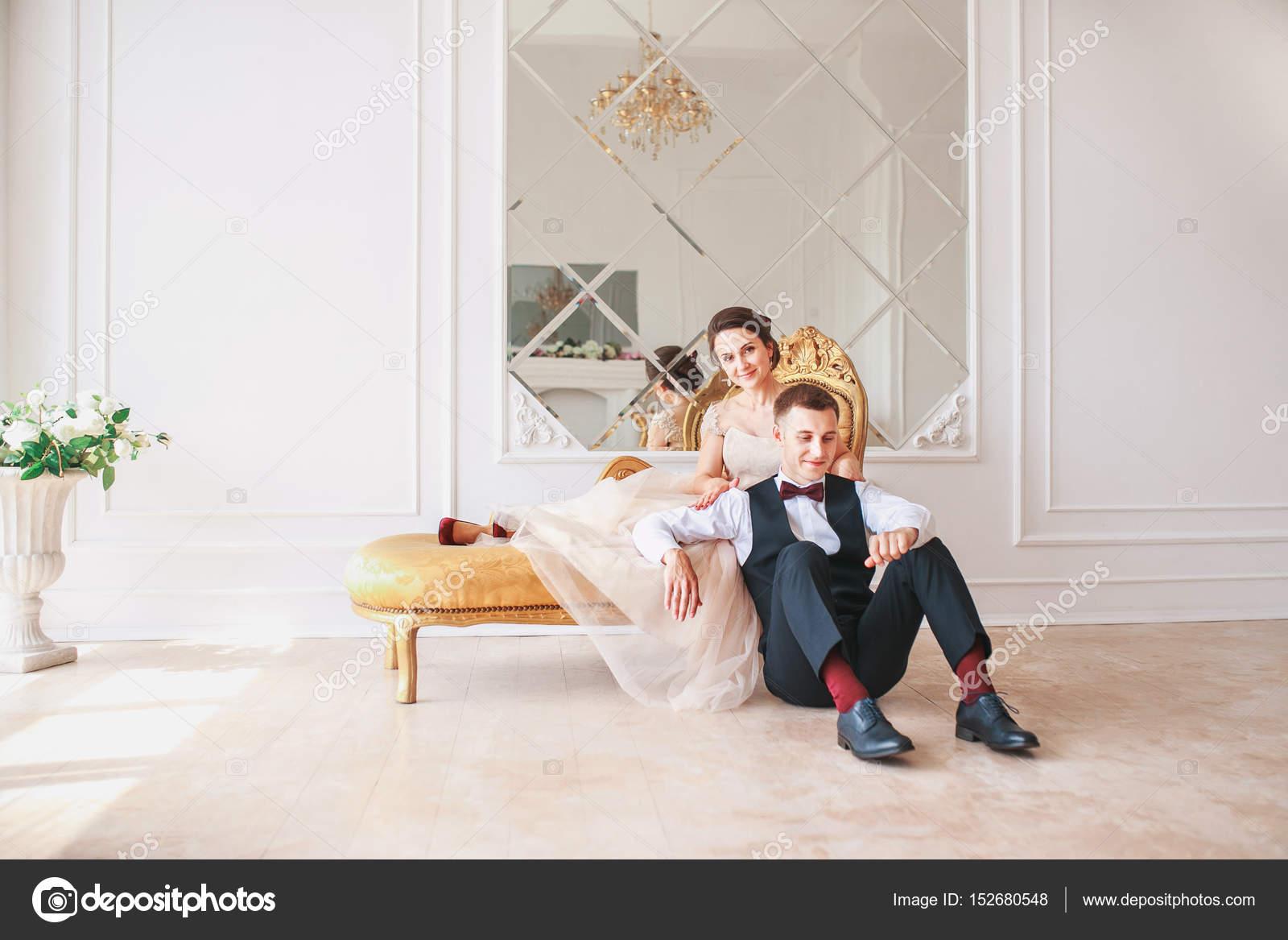 Braut im Kleid und der Bräutigam im schwarzen Anzug auf Sofa im ...
