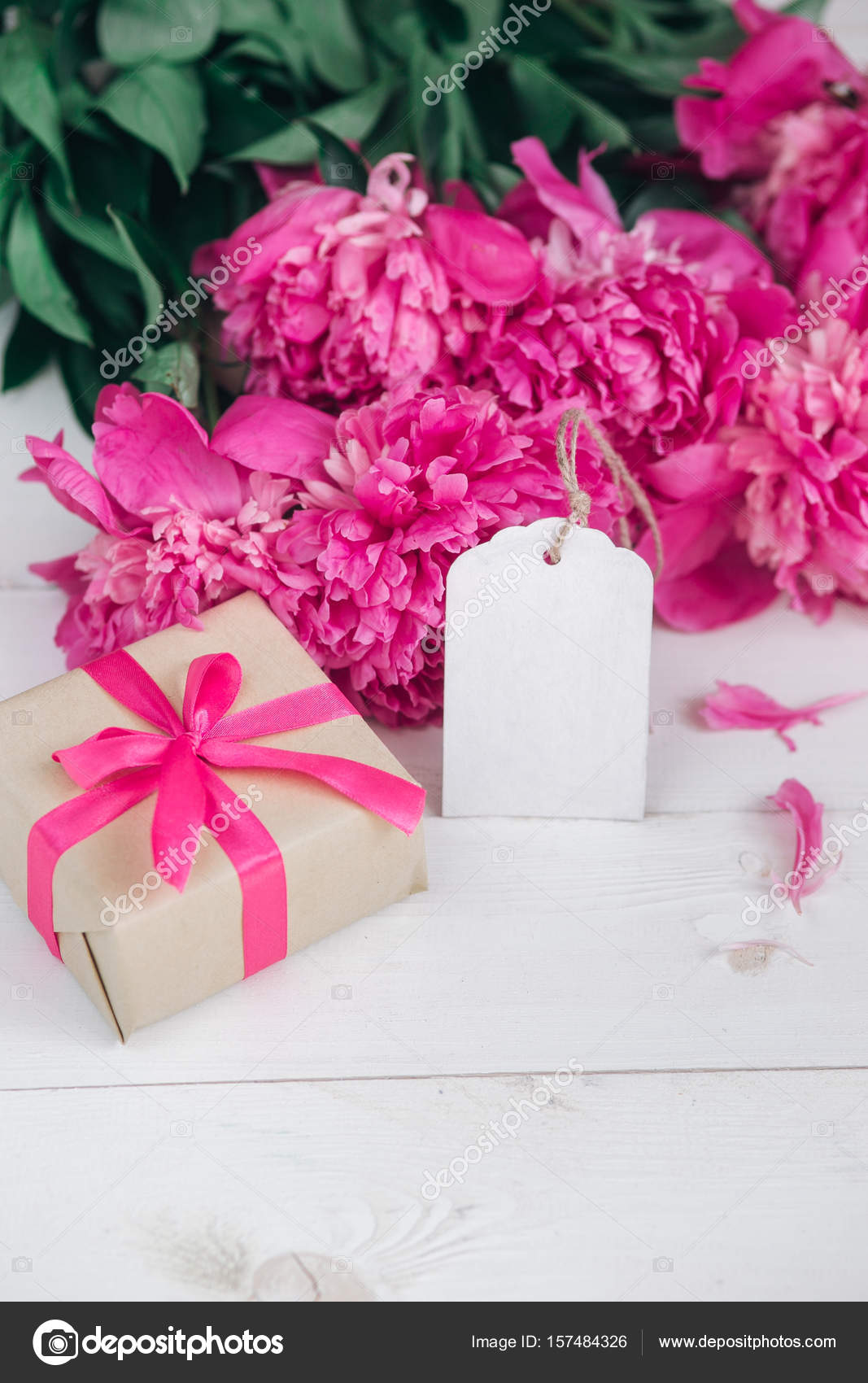 Pink peonies flowers and empty tag on aged wooden background. Top ...