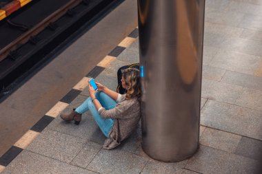 young blonde woman sitting and listening to music while waiting for subway at station