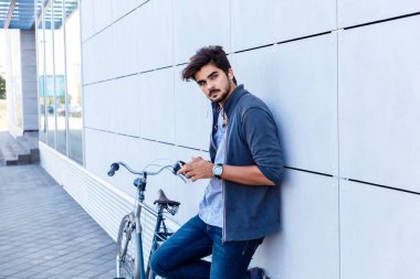 young man listening music at smartphone while standing near bicycle in city