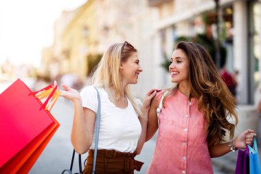 Happy young women with colorful shopping bags in city