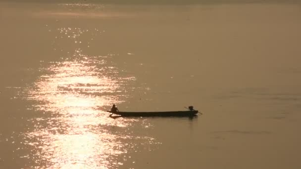 Thai and laos people riding long tail boat for catch fishing and reflection light surface water of Mekhong River and lighting of Sun in morning time at Mukdahan, Thailand