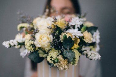 Woman florist making a lovely flower composition in a flower sho