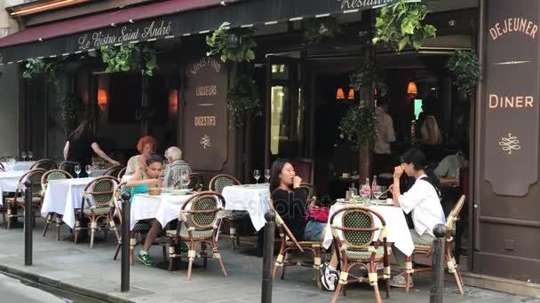 Lidí, kteří sedí v pařížské kavárně