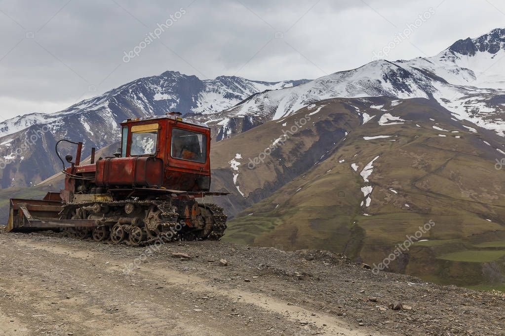 Old Soviet caterpillar tractor in the background of snow-capped