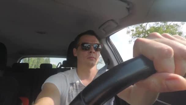 Ein Mann fährt Auto. zum Zeitpunkt der Bewegung entfernt Sonnenbrille.