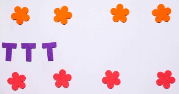 The letter T flies from side to side. Top and bottom flowers are moving