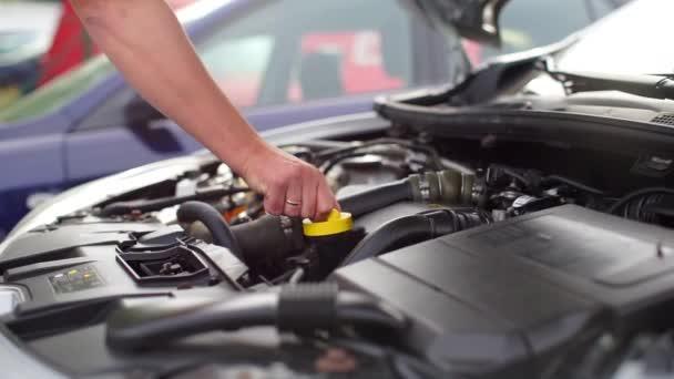 řidič otevírá kryt motorového oleje