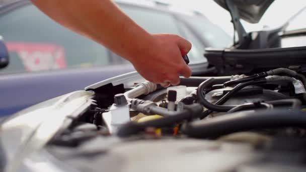 mechanik odšroubuje a otáčí uzávěrem motorové kapaliny