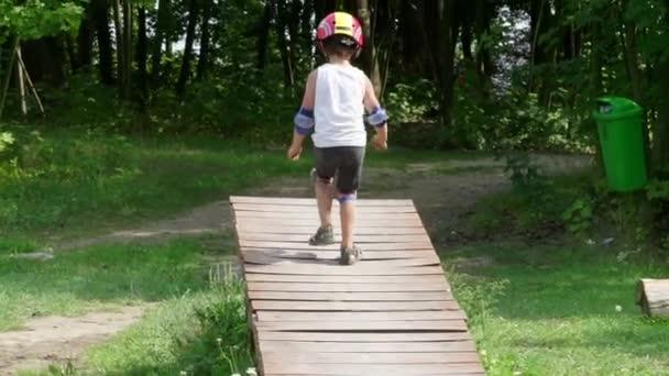 Junge läuft ohne Fahrrad auf Hindernisschaukel auf Radweg