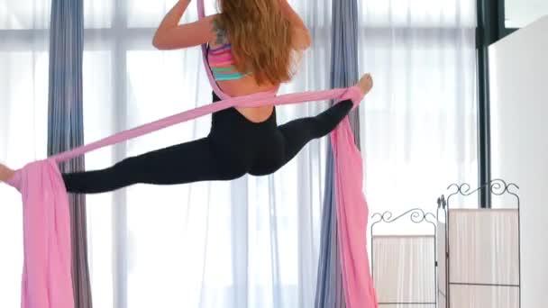Žena tančí na látce zavěšené ze stropu..