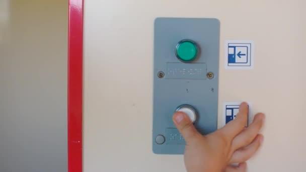 Detailní záběr dvou tlačítek. Dítě jednou rukou stiskne jedno tlačítko.