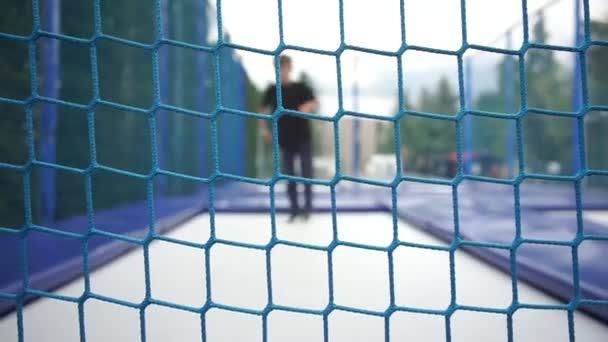 playground net, child jumps on a trampoline