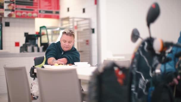 Žena bez rukou obědvá v kavárně v kanceláři..
