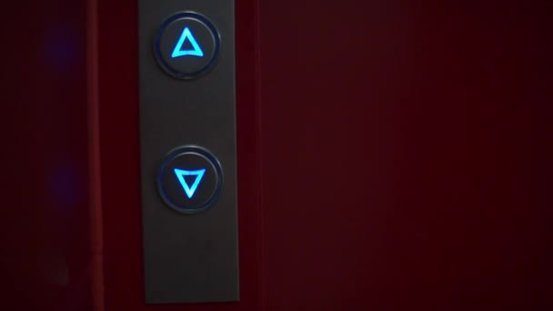 Tlačítka výtahu v noční hale hotelu.