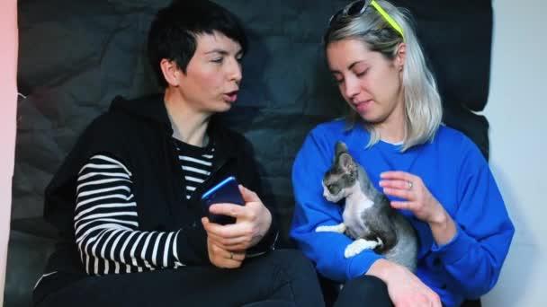 zwei Mädchen auf einer Party mit einer Katze. Mädchen machen Fotos mit dem Smartphone.