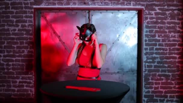 Mädchen probiert eine Katzenmaske auf ihrem Gesicht an, bevor sie in einem Nachtclub spricht