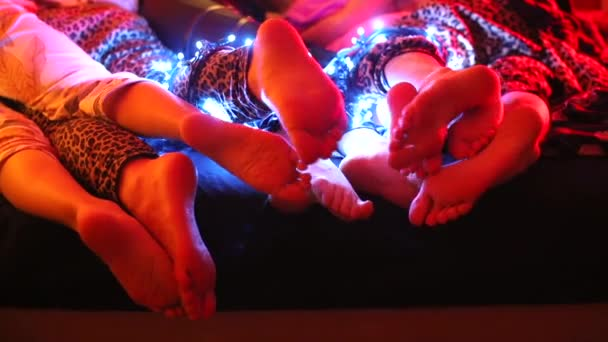 Füße von Swingern liegen auf einem Bett in einem Nachtclub bei einer Party.