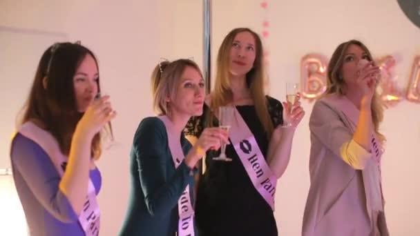 Részeg lányok pezsgős poharakkal a kezükben egy partin..