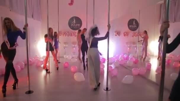 Girls in a dance studio make body movements near the pylon