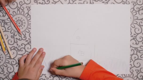 dítě kreslí tužkou, dům je nakreslen