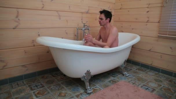 Egy férfi ül a fürdőszobában, beállítja a víz hőmérsékletét, és énekel egy dalt..