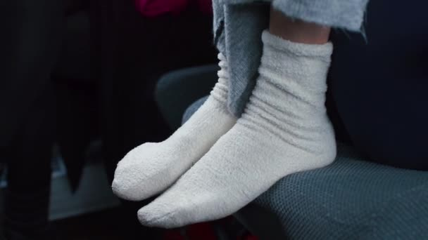 Closeup of the legs of a girl in white socks.