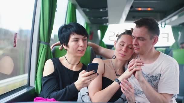 An LGBT family travels on the passenger seats of a bus while traveling.