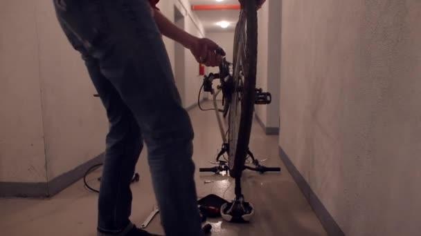 Egy férfi leveszi a hátsó kereket a bicikliről a kezével..